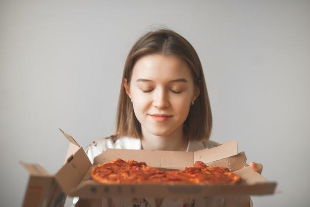 여자의 초상화는 그녀의 손에 뜨거운 피자 한 상자를 들고 눈을 감고 피자 냄새를 맡습니다.