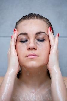 앉아서 화장에서 그녀의 얼굴을 씻는 목욕에 있는 여자의 초상화. 눈 주위에는 마스카라로 인한 검은 반점이 있습니다. 그녀의 눈에 반점을 지우는 젊은 여성의 클로즈업