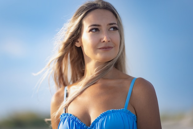 푸른 바다와 맑은 하늘을 배경으로 파란색 수영복과 흰색 셔츠를 입은 소녀의 초상화