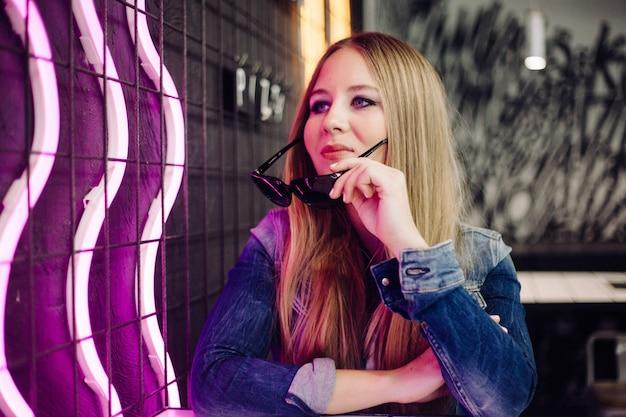 市内のカフェ、ネオンの照明、若者スタイルの女の子の肖像画