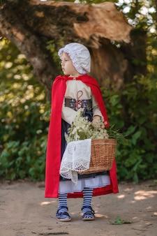 Портрет девушки в сказочном костюме красной шапочки с корзиной и цветами в лесу