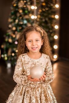 크리스마스 트리 배경에 금색 드레스를 입은 소녀의 초상화..