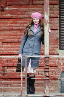 旧市街の通りに灰色のコートとピンクのベレー帽の少女の肖像画