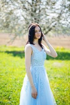 꽃이 만발한 나무에 머리를 장식한 밝은 여름 파란색 긴 드레스를 입은 소녀의 초상화.