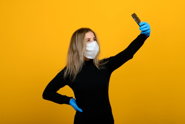ゴム手袋をはめる医療用マスクの少女の肖像画。