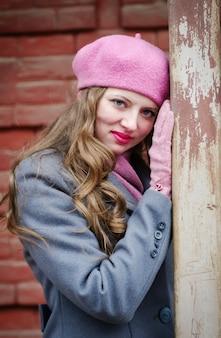 ピンクのベレー帽とグレーブルーのコートを着た女の子の肖像画