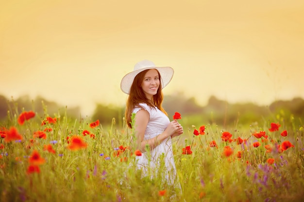 Портрет девушки в маковом поле на закате в белом платье и шляпе
