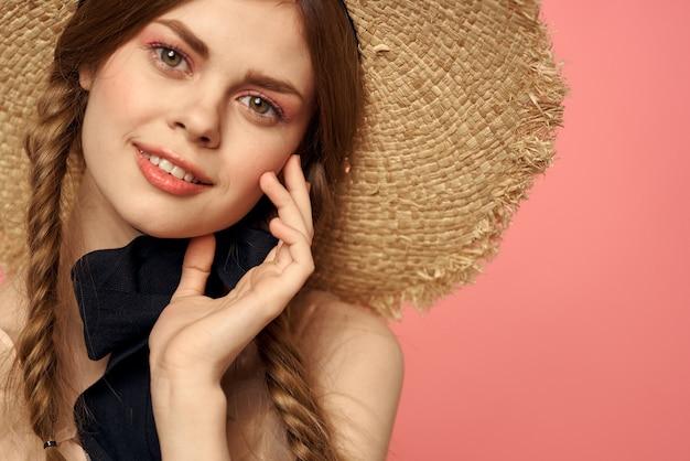 Портрет девушки в соломенной шляпе на розовом