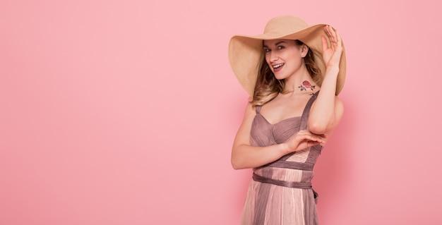 Портрет девушки в летней шляпе и платье на розовой стене