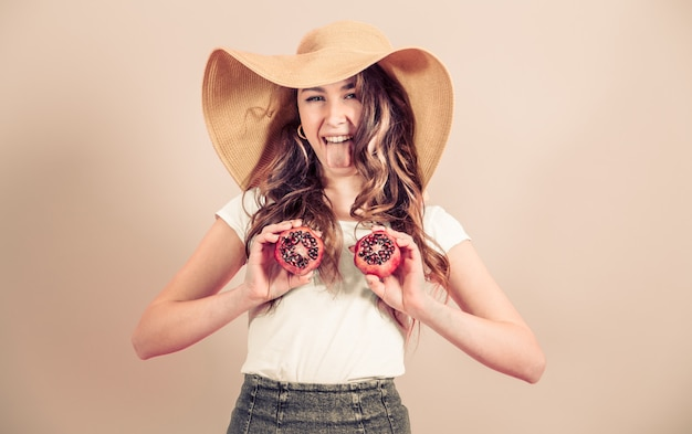 Портрет девушки в летней шапке с фруктами на цветном фоне