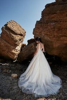 Портрет девушки в свадебном платье великолепно позирует фотографу на пляже. невеста на скалах