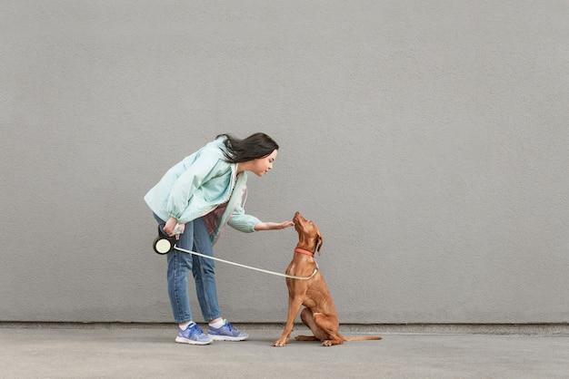 Портрет девушки в повседневной одежде держит собаку на поводке и играет