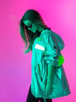 Портрет девушки в солнечных очках на розовом фоне