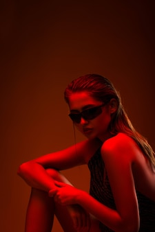 Портрет девушки в солнечных очках с красным светом на красной стене.