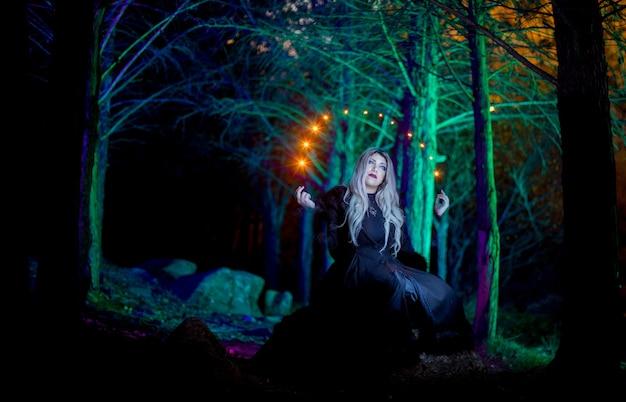 Портрет девушки в темном лесу с яркими огнями вокруг нее