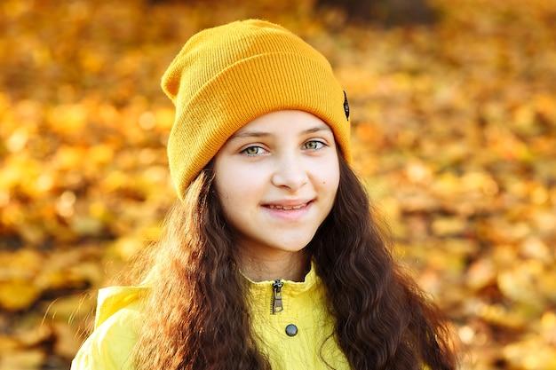 공원 근접 촬영에서 가을에 노란 옷을 입은 소녀의 초상화