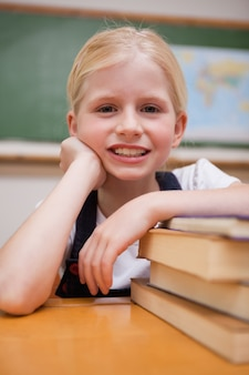 Portrait of a girl leaning on books in a classroom