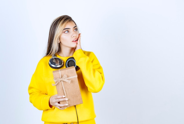 Портрет девушки-модели, держащей бумажную коробку с бантом, изолированную над белой стеной