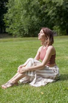 緑のフィールドに女の子の肖像画。女性は草の上に座って目を閉じています。夏の日。リラクゼーション。