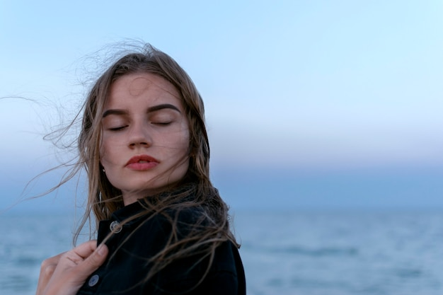 ビーチで女の子の肖像画。日没。風になびく髪