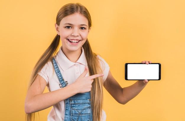 Портрет девушки, указывая пальцем на смартфон, показывая белый экран стоя на желтом фоне