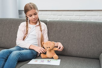 Portrait of a girl showing family drawing paper to her teddy bear