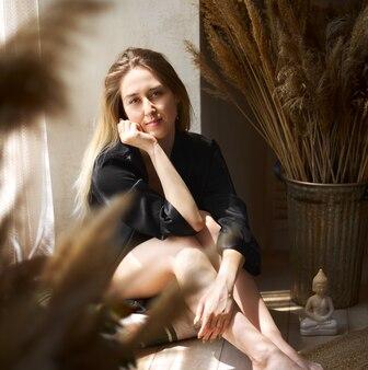 집 창가에 앉아 카메라를 바라보는 소녀의 초상화. 검은 잠옷을 입은 여자.