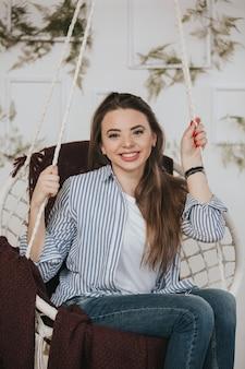 Портрет девушки, сидящей в подвесном кресле
