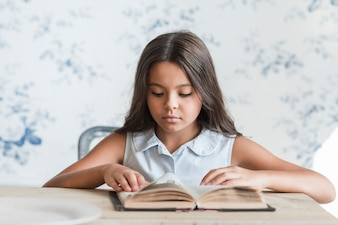 Portrait of a girl sitting in front of wallpaper reading book