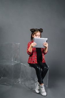 Portrait of a girl sitting on transparent block looking at digital tablet against gray background
