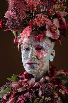 Портрет девушки, намазанной глиной, в зацементированном платье. на голове девушки портрет живых цветов.