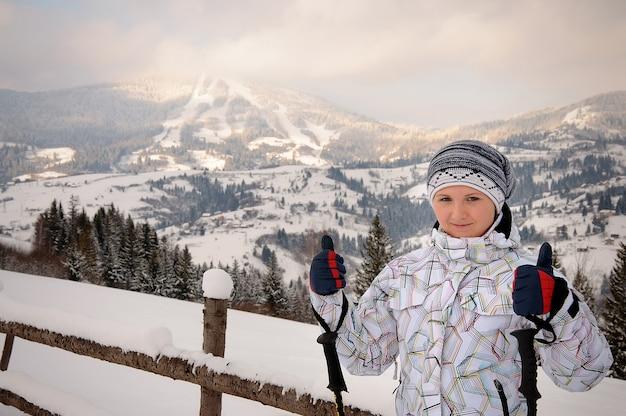 スキーの上に立って、雪に覆われた山と森に対してポーズの女の子の肖像画。カルパティア山脈の山の冬の自然。女性はスキーヤーです。