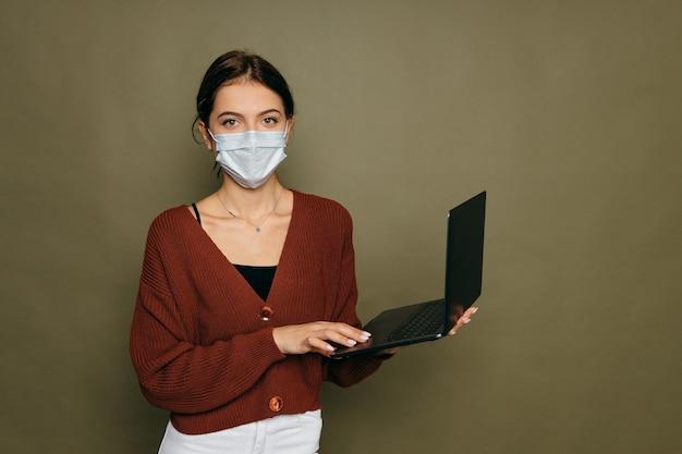 Портрет студентки в защитной маске с ноутбуком на зеленом фоне. фото высокого качества