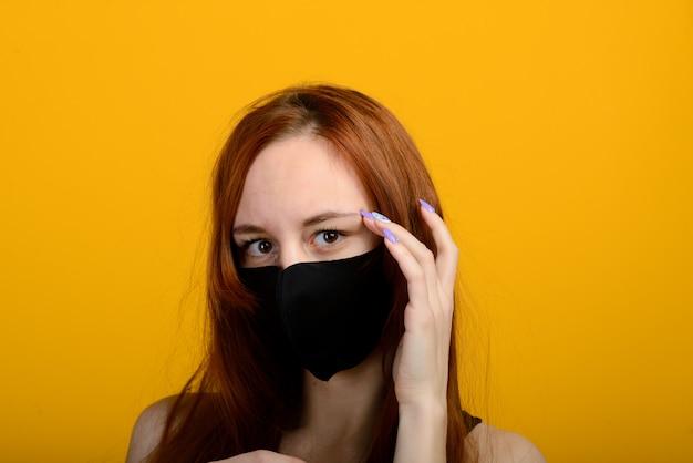黄色の背景にフェイスマスクを着ている少女の肖像画