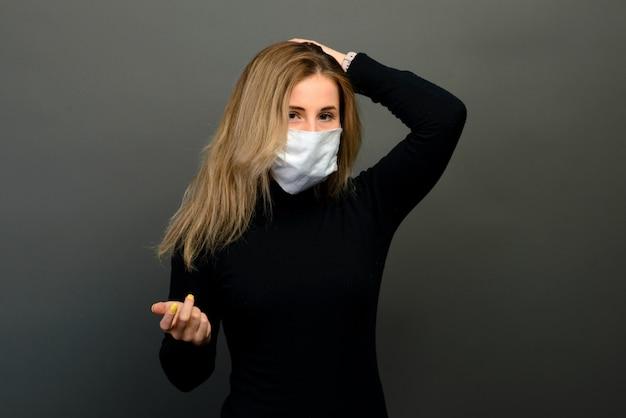 Портрет девушки в медицинской маске на сером фоне