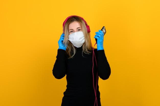 黄色の背景に医療マスクを着ている少女の肖像画