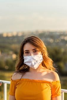街でフェイスマスクを身に着けている女の子の肖像画