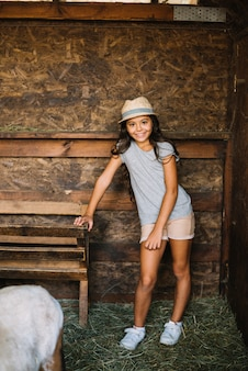Portrait of a girl wearing hat standing in the barn