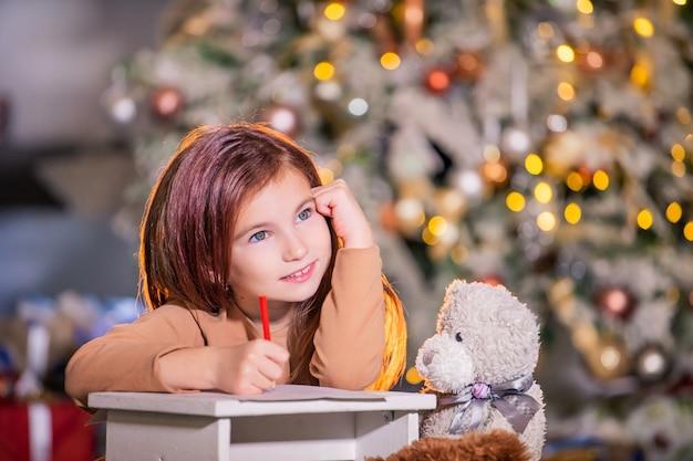 サンタクロースに手紙を書いている大きな手紙を持つ少女の肖像画 Premium写真