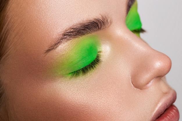薄緑色のメイクアップとマットな口紅でバーガンディの唇を持つ少女の肖像画。
