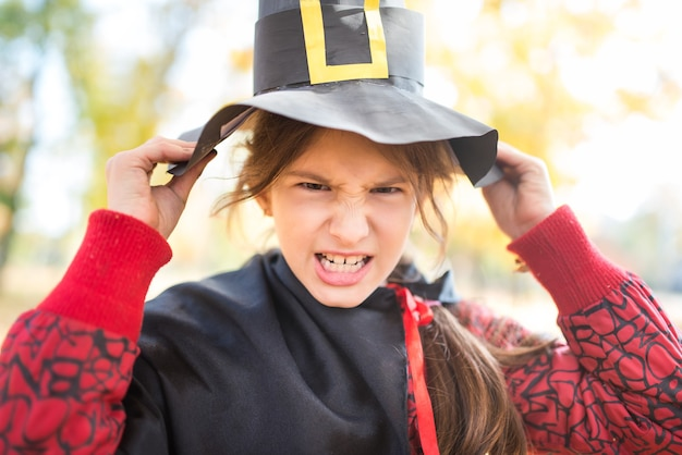 秋の公園で黒い帽子をかぶった不吉な顔を持つ少女の肖像画