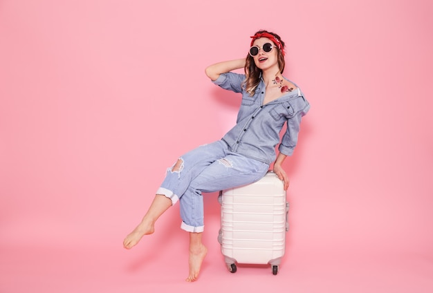 ピンクの壁にスーツケースを持つ少女の肖像画