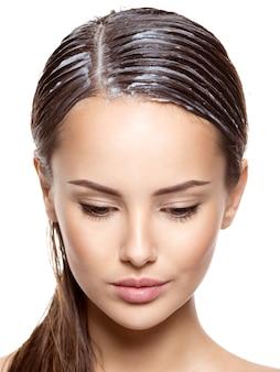 Портрет девушки с нанесенной краской для волос на белой стене