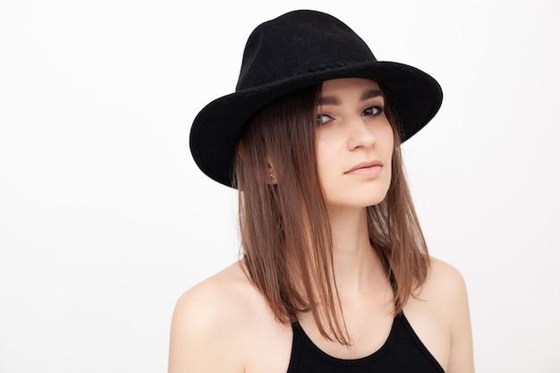スタジオで黒い帽子をかぶってカメラで見ている美しい目を持つ少女の肖像画