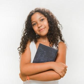 彼女の腕を折りたたむ本を持つ女の子の肖像