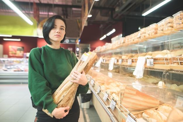 Портрет девушки с багетом хлеба в руках супермаркета. красивая девушка позирует в хлебном отделе супермаркета.