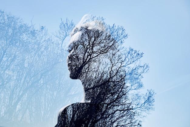 나무 왕관에 대한 이중 노출을 가진 소녀의 초상화. 푸른 하늘을 가진 여성의 섬세하고 신비한 초상화