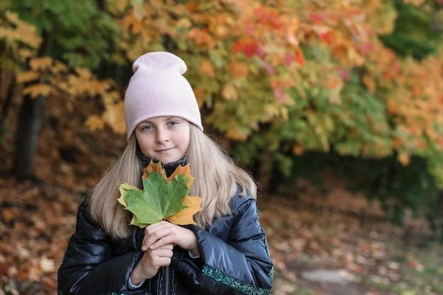 落ちたカエデの葉を持つ少女の肖像画を手に