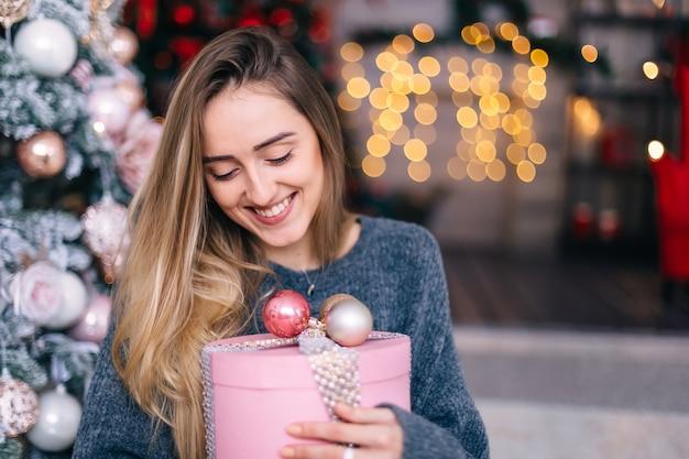 クリスマスツリーと花輪の背景に優しい化粧と彼女の手に贈り物を持っている女の子の肖像画。
