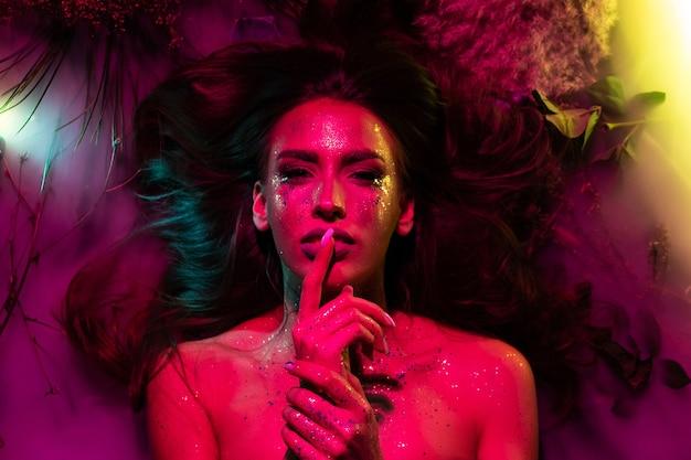 ピンクの創造的な光の中で彼女の体にキラキラと女の子の肖像画。女の子は花と煙の中に横たわっています。